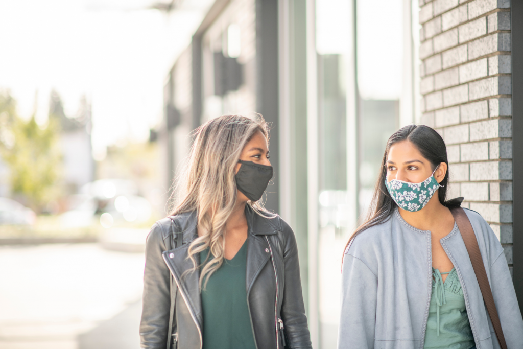 two women walking outside and wearing face masks